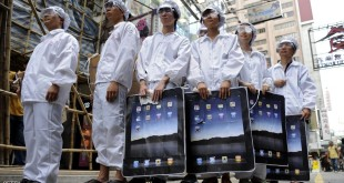 """Participants dressed up to represent Foxconn workers take part in a protest against Taiwanese technology giant Foxconn, which manufactures Apple products in mainland China, outside an Apple retail outlet in Hong Kong on May 7, 2011.  Taiwanese technology giant Foxconn treats its workers like """"machines"""" a Hong Kong based labour group said on May 3, after a survey based on interviews with the firm's workers in mainland China. At least 13 Foxconn employees died in apparent suicides last year, which rights activists blamed on tough working conditions in a case that highlighted the challenges faced by millions of Chinese factory workers.   AFP PHOTO / Antony DICKSON (Photo credit should read ANTONY DICKSON/AFP/Getty Images)"""