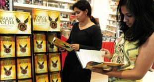 """Indian women pose for a photograph as they read part of J.K. Rowlings new book """"Harry Potter and the Cursed Child' during an event to mark the book launch at a mall in Chennai on July 31, 2016. Harry Potter magic hit Asia, as aspiring witches and wizards crowded into bookstores to get their hands on the first copies of a new play that imagines the hero as an adult. / AFP / ARUN SANKAR        (Photo credit should read ARUN SANKAR/AFP/Getty Images)"""