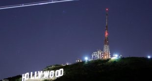 """LOS ANGELES, CA - NOVEMBER 16:  The Hollywood Sign is illuminated by the spotlight of a helicopter streaking past the sign at night on November 16, 2005 in Los Angeles, California. The historic landmark is undergoing a month-long makeover; erected in 1923 as a giant ad for a housing development and originally read """"Hollywoodland"""", the sign with letters that are 45 feet tall and 36 feet wide was declared a Los Angeles Cultural Historical Monument in 1973.  (Photo by David McNew/Getty Images)"""