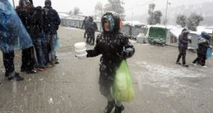 "A migrant walks after receiving food during snowfall at the Moria hotspot on the Greek island of Lesbos, on January 9, 2017. With more than 60,000 mainly Syrian refugees on its territory, Greece has moved many migrants to prefabricated houses and heated tents, but  on the island of Lesbos in Moria hotspot there are ""more than 2,500 people living in tents, without hot water or heating, including women, children and handicapped people,"" said Apostolos Veizis from the charity Doctors Without Borders. / AFP / STR        (Photo credit should read STR/AFP/Getty Images)"
