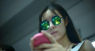 A woman wearing sunglasses plays with her mobile phone on a subway train in Beijing on June 24, 2014.    AFP PHOTO / WANG ZHAO        (Photo credit should read WANG ZHAO/AFP/Getty Images)