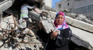 """Palestinian woman Jihan Abu Muhsen collects bricks for sale with her son Mohammad from the ruins of a house destroyed during the 2014 war in Khan Younis in the southern Gaza Strip March 8, 2016. Abu Muhsen gathers bricks from the sites of demolished buildings and sells them to recycling factories. She earns around 20 shekels ($5) a day and her 10-year-old son Mohammad helps her when he is not at school. REUTERS/Ibraheem Abu Mustafa    SEARCH """"GAZA BRICK"""" FOR THIS STORY. SEARCH """"THE WIDER IMAGE"""" FOR ALL STORIES."""