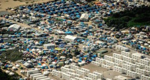 """(FILES) This file photo taken on August 16, 2016 shows an aerial view of tents in the """"jungle"""" camp in Calais, northern France. The """"Jungle"""" camp in the northern French town of Calais, home to thousands of migrants hoping to reach Britain, will be gradually dismantled, the country's interior minister vowed on September 2, 2016. Interior Minister Bernard Cazeneuve told a regional paper that he would press ahead with the closure """"with the greatest determination"""", dismantling the site in stages while creating accommodation for thousands elsewhere in France """"to unblock Calais"""".  / AFP PHOTO / PHILIPPE HUGUEN"""