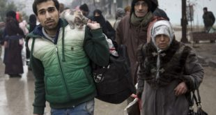 TOPSHOT - Syrians leave a rebel-held area of Aleppo towards the government-held side on December 13, 2016 during an operation by Syrian government forces to retake the embattled city. UN chief Ban Ki-moon expressed alarm over reports of atrocities against civilians Monday, as the battle for Aleppo entered its final phase with Syrian government forces on the verge of retaking rebel-held areas of the city.   / AFP PHOTO / KARAM AL-MASRI