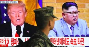 A South Korean soldier walks past a television screen showing pictures of US President Donald Trump (L) and North Korean leader Kim Jong Un at a railway station in Seoul on March 9, 2018.  US President Donald Trump agreed on March 8 to a historic first meeting with North Korean leader Kim Jong Un in a stunning development in America's high-stakes nuclear standoff with North Korea. / AFP / Jung Yeon-je