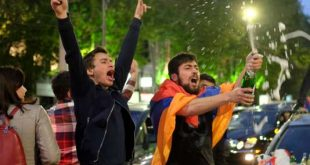 A man covered with a national flag waves an opened bottle of a sparkling wine celebrating Armenian Prime Minister's Serzh Sargsyan's resignation in Republic Square in Yerevan, Armenia, Monday, April 23, 2018. Sargsyan resigned unexpectedly Monday to quell massive anti-government protests over what critics feared was his effort to seize power for life. (Hrant Khactaryan/PAN Photo via AP)