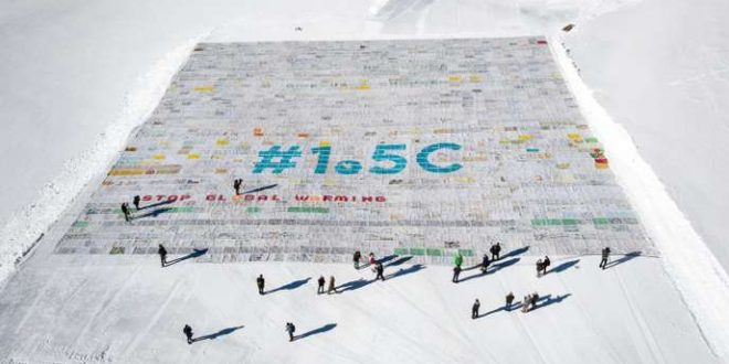 """TOPSHOT - An aerial view shows a massive collage of 125,000 drawings and messages from children from around the world about climate change seen rolled out on the Aletsch Glacier at an altitude of 3,400 metres near the Jungfraujoch in the Swiss Alps smashing the world record for the giant postcard, on November 16, 2018. The mosaic of postcards, measuring 2,500 square metres (26,910 square feet), was laid out in the snow to """"boost a global youth climate movement ahead of the next global climate conference (COP24) in Poland"""", next month, said the WAVE foundation, which organised the event in cooperation with Swiss authorities. / AFP / Fabrice COFFRINI"""