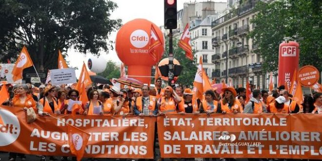"CFDT unionist medical staff demonstrate on May 22, 2018 in Paris during a nationwide day protest by French public sector employees and public servants against the overhauls proposed by French President, calling them an ""attack"" by the centrist leader against civil services as well as their economic security. (Photo by Bertrand GUAY / AFP)"