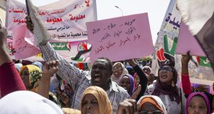 """Protesters carry posters in Arabic that say, """"Freedom, justice, and peace, and the revolution is the choice of the people,"""" at the sit-in outside the military headquarters, in Khartoum, Sudan, Thursday, May 2, 2019. Sudan's protesters are holding a mass rally to step up pressure on the military to hand power to civilians following last month's overthrow of President Omar al-Bashir. (AP Photos/Salih Basheer)"""