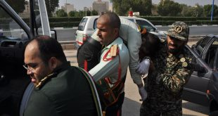 """CORRECTION - This picture taken on September 22, 2018 in the southwestern Iranian city of Ahvaz shows an Iranian soldier carrying an ijured comrade at the scene of an attack on a military parade that was marking the anniversary of the outbreak of its devastating 1980-1988 war with Saddam Hussein's Iraq. - At least eight troops were killed on September 22 in an attack on a military parade in the southwestern province of  Khuzestan, the province's deputy governor Ali-Hossein Hosseinzadeh said. (Photo by Behrad GHASEMI / ISNA / AFP) / """"The erroneous mention[s] appearing in the metadata of this photo by Shayan HAJI NAJAF has been modified in AFP systems in the following manner: [Behrad GHASEMI] instead of [Shayan HAJI NAJFI]. Please immediately remove the erroneous mention[s] from all your online services and delete it (them) from your servers. If you have been authorized by AFP to distribute it (them) to third parties, please ensure that the same actions are carried out by them. Failure to promptly comply with these instructions will entail liability on your part for any continued or post notification usage. Therefore we thank you very much for all your attention and prompt action. We are sorry for the inconvenience this notification may cause and remain at your disposal for any further information you may require."""""""