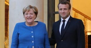 French President Emmanuel Macron (R) and German Chancellor Angela Merkel pose upon her arrival at the Elysee Palace for a working dinner ahead of the EU summit in Paris on October 13, 2019. (Photo by ludovic MARIN / AFP)