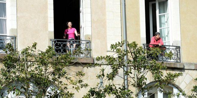 Une jeune femme fait du vélo d'appartement à sa fenêtre lors de cette deuxième journée du confinement. L'état d'urgence sanitaire impose des mesures radicales de confinement pour lutter contre la propagation du coronavirus Covid-19
