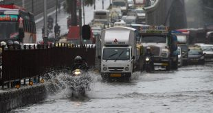 Vehicles drive through a waterlogged road after a heavy monsoon rainfall in Mumbai on July 16, 2021. (Photo by Punit PARANJPE / AFP)