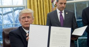US President Donald Trump holds up an executive order withdrawing the US from the Trans-Pacific Partnership after signing it alongside White House Chief of Staff Reince Priebus (R) in the Oval Office of the White House in Washington, DC, January 23, 2017. Trump the decree Monday that effectively ends US participation in a sweeping trans-Pacific free trade agreement negotiated under former president Barack Obama. / AFP PHOTO / SAUL LOEB