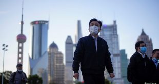 FILE PHOTO: People wear protective face masks, following an outbreak of the novel coronavirus disease (COVID-19), at Lujiazui financial district in Shanghai, China March 19, 2020. REUTERS/Aly Song - RC22NF9MD3D3/File Photo