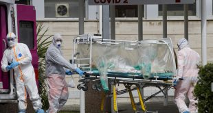 A patient in a biocontainment unit is carried on a stretcher from an ambulance at the Columbus Covid 2 Hospital in Rome, on Tuesday. Italy's health system is straining to keep up with quickly rising coronavirus cases.