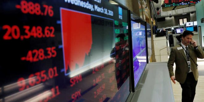 A trader is reflected in a board at the New York Stock Exchange showing the day's numbers as markets continue to react to the coronavirus disease (COVID-19) inside of the NYSE in New York, U.S., March 18, 2020.  REUTERS/Lucas Jackson
