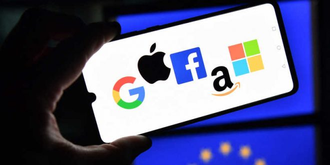 An illustration picture taken in London on December 18, 2020 shows the logos of Google, Apple, Facebook, Amazon and Microsoft displayed on a mobile phone with an EU flag displayed in the background. (Photo by JUSTIN TALLIS / AFP)