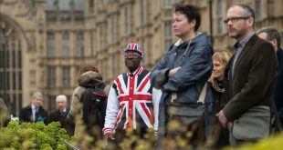TOPSHOT - A man wearing clothing featuring the Union flag stands in front of the Houses of Parliament in London  on March 29  2017  shortly before British Prime Minister Theresa May announced to the House of Commons that Article 50 of the Lisbon Treaty had been triggered  formally starting Britain s withdrawl from the European Union  EU    Britain formally launched the process for leaving the European Union on March 29  a historic move that has split the country and thrown into question the future of the European project    AFP PHOTO   OLI SCARFF