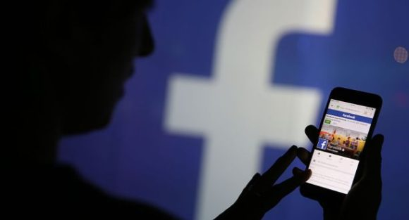 A woman checks the Facebook Inc. site on her smartphone whilst standing against an illuminated wall bearing the Facebook Inc. logo in this arranged photograph in London, U.K., on Wednesday, Dec. 23, 2015. Facebook Inc.s WhatsApp messaging service, with more than 100 million local users, is the most-used app in Brazil, according to an Ibope poll published on Dec. 15. Photographer: Chris Ratcliffe/Bloomberg via Getty Images
