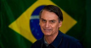 Brazil's right-wing presidential candidate for the Social Liberal Party (PSL) Jair Bolsonaro walks in front of the Brazilian flag as he prepares to cast his vote during the general elections, in Rio de Janeiro, Brazil, on October 7, 2018. Polling stations opened in Brazil on Sunday for the most divisive presidential election in the country in years, with far-right lawmaker Jair Bolsonaro the clear favorite in the first round. About 147 million voters are eligible to cast ballots and choose who will rule the world's eighth biggest economy. New federal and state legislatures will also be elected. / AFP / Mauro PIMENTEL