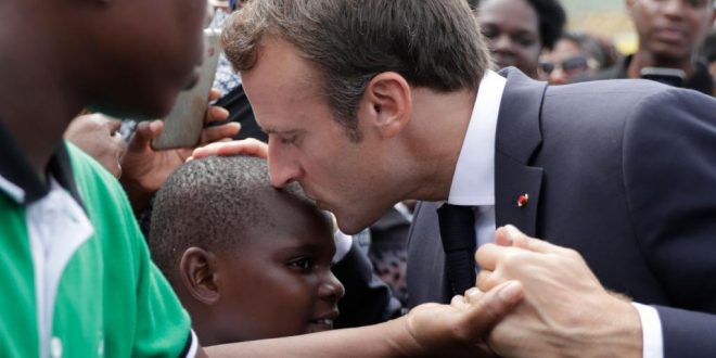 French president Emmanuel Macron (C) kisses a boy as he visits Quartier d'Orleans, on September 29, 2018 on the French Caribbean island of Saint-Martin, during a trip in the French West Indies, one year after Hurricane Maria damaged the Island. (Photo by Thomas SAMSON / various sources / AFP)