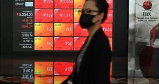 A woman walks past a large screen showing the trading numbers on the Indonesia Stock Exchange (IDX) in Jakarta on March 9, 2020. - Equity markets collapsed on March 9 as the rapidly spreading coronavirus fans fears for the global economy, while a crash in oil prices added to the panic with energy firms taking a hammering and wiping hundreds of billions off valuations. (Photo by ADEK BERRY / AFP)